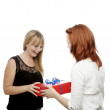 Young beautiful red and blond haired girls give gift box — Stock Photo