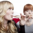 Stock Photo: Young beautiful blond and red haired girls drink champagne on re