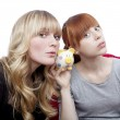 Young beautiful blond and red haired girls ears on moneypig on r — Stock Photo