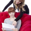 Young beautiful blond and red haired girls on red sofa show lett — Stock Photo