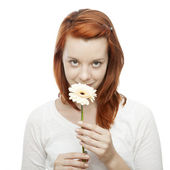 Young beautiful red haired girl smelling on a flower — Stock Photo