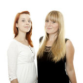 Young beautiful red and blond haired girls stand together — Stock Photo