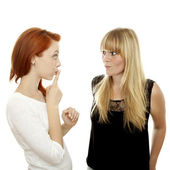 Young beautiful red and blond haired girls with finger on mouth secret — Stock Photo