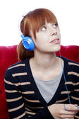 Young beautiful red haired girl on red sofa listen to great musi — Stock Photo