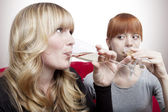 Young beautiful blond and red haired girls drink champagne on re — Stock Photo