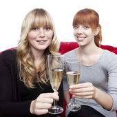 Young beautiful blond and red haired girls with champagne on red — Stock Photo