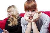 Young beautiful blond and red haired girls sitting on red sofa a — Stock Photo