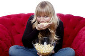 Young blond haired girl eat a hand of popcorn on red sofa in fro — Stock Photo