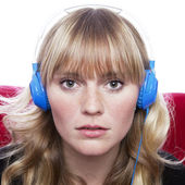 Stunning young blond haired girl with headphones on red sofa in — Stock Photo