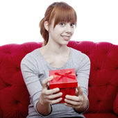 Young beautiful red haired girl on red sofa has a present box fo — Stock fotografie