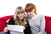 Young beautiful blond and red haired girls on red sofa reading l — Stock Photo