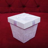 Beautiful white gift box with ribbon on top of red sofa backgrou — Stockfoto