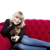 Young blond haired girl on red sofa happy with remote control in — Stock Photo