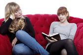 Lindas loiras e vermelhas cabelos jovens lerem um livro no vermelho para — Foto Stock