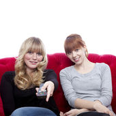 Young beautiful blond and red haired girls on red sofa in front — Stock Photo
