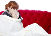 若い美しい赤い髪の女の子赤いソファの上の前に病気であります。 — ストック写真