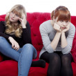 Stock Photo: Young beautiful blond and red haired girls are bored and depress