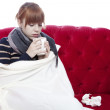 Young beautiful red haired girl on red sofa has a cold in front  — Stock Photo