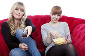 Young beautiful blond and red haired girls on red sofa with remo — Stock Photo
