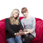 Young beautiful blond and red haired girls on red sofa wondering — Stok fotoğraf