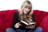 Jovem garota de cabelo loira no sofá vermelho ler um livro na frente de whit — Foto Stock