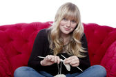 Young blond haired girl on red sofa knitting in front of white b — Stock Photo