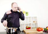 Man taking a call on his mobile while cooking — Stock Photo