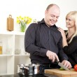 Affectionate couple preparing dinner — Stock Photo