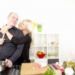Romantic happy couple preparing a meal — Stock Photo