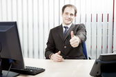 Confident businessman giving a thumbs up — Stock Photo