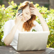 Smiling woman sitting in the garden using a mobile — Stock Photo
