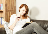 Pretty young redhead woman reading a book — Stock Photo