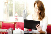 Pretty young woman browsing her tablet-pc — Stock Photo