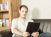 Man relaxing reading an e-book — Stock Photo