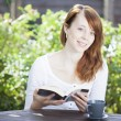 Pretty young woman reading outdoors — Stock Photo