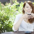 Young woman relaxing with a mug of coffee — Stok fotoğraf
