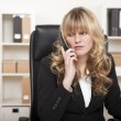 Pretty businesswoman listening to a phone call — Stok fotoğraf