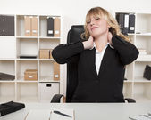 Overworked businesswoman stretching her neck — Stock Photo