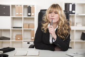 Young businesswoman sitting thinking — Stock Photo