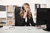 Businesswoman talking on the phone while typing — Stock Photo
