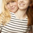 Stock Photo: Red and blond haired girls friends laugh and hug
