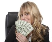 Smirking businesswoman with a fistful of dollars — Stock Photo