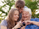 Young and old woman examine the image in phone — Stock Photo