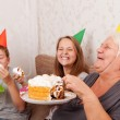 Senior woman and its grandsons with birthday cake — Stock Photo #24089229