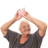 Portrait of a happy mature woman holding piggy bank isolated aga — Stock Photo