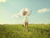 The young beautiful girl in a white dress enjoys a wind, the sun — Stock Photo
