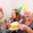 Senior woman and its grandsons with birthday cake — Stock Photo