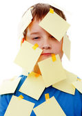 Boy with memo posts on his face — Stock Photo