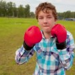 The boy in boxing gloves in a meadow — Stock Video