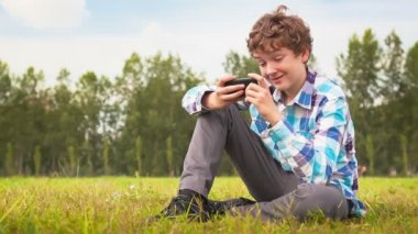Man sitting on a green meadow with a cellphone — Stock Video